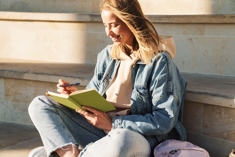 Cheerful young blonde girl taking notes while sitting